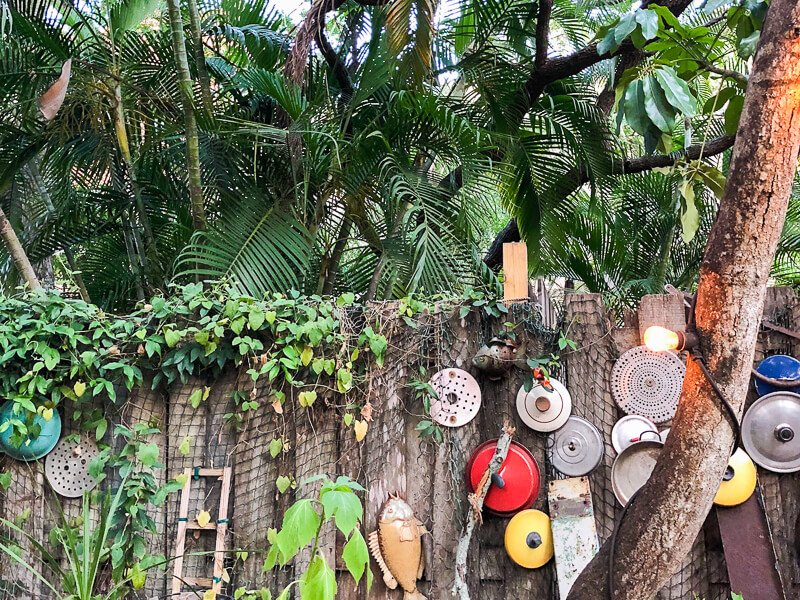 Wooden Fence with hanging pot lids and palm trees behind it