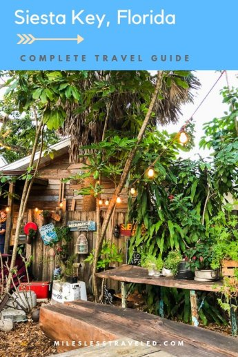 Patio with wooden building and stringlights and trees with text overlay Siesta Key Florida Complete Travel Guide mileslesstraveled.com
