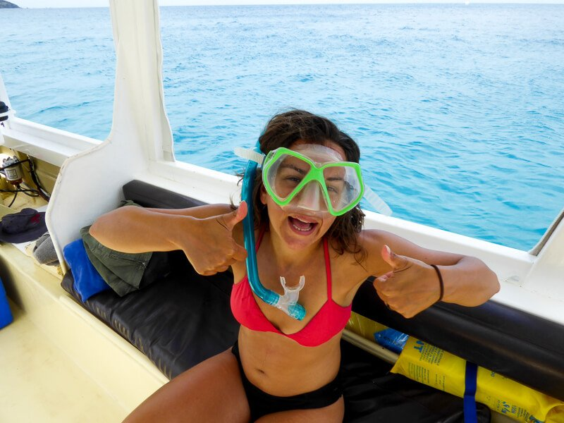 Woman on boat with green snorkel mask and blue snorkel giving thumbs up