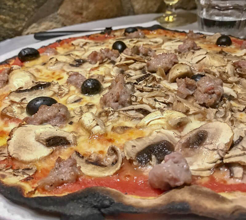 Closeup of sausage and black olive thin crust neopolitan style pizza in trastevere rome
