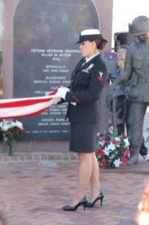 Woman in military dress folding flag