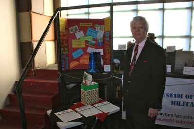 Allen Olson standing next to poster