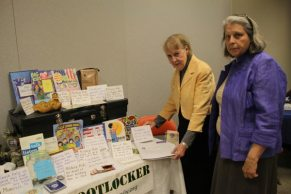 Joan Olson and Caroline LeBlanc standing by Operation Footlocker table