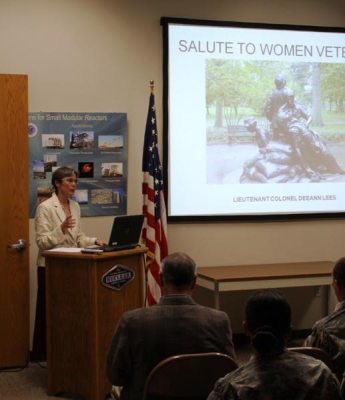 Circe Olson at podium with Salute to Women Veterans on screen