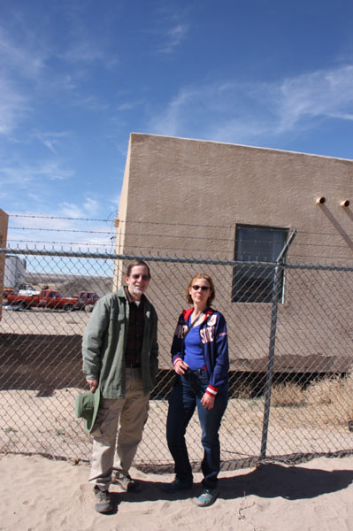 Circe Olson Woessner and man standing in front of chain link fence with small adobe house in background