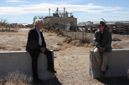 Allen Olson and Paul Silva sitting on barricades with houses and construction materials in background