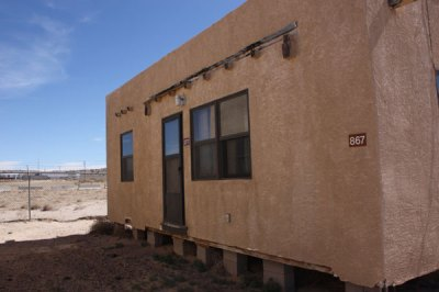 Small adobe house with 867 house number