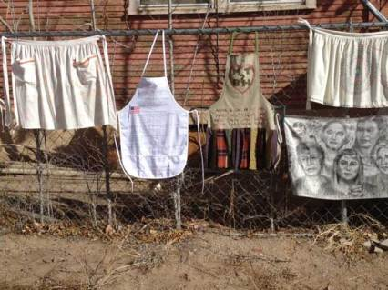 Aprons hanging on fence