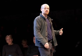Telling Project: Man with glasses and sweat jacket standing on stage