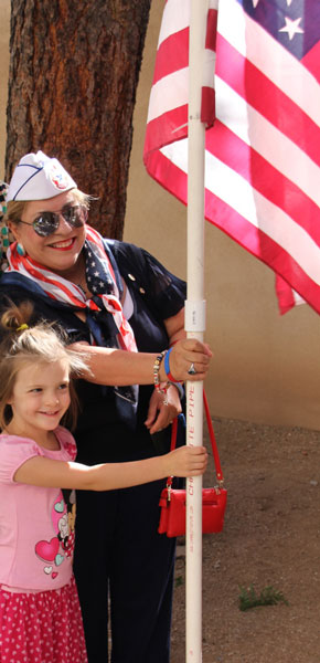 Female in service organization hat and young girl holding flag