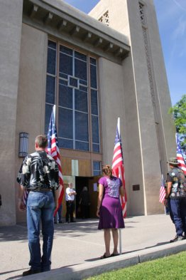People holding flags in front of building