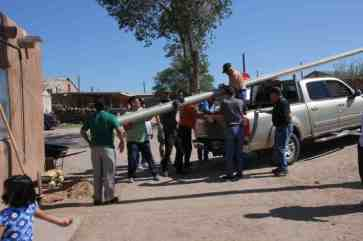 Men lifting large flagpole out of truck