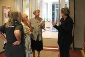 4 women talking, one holding script