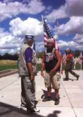 Veteran in service organization hat talking to man in shorts and black T-shirt with logo with flags in backgound