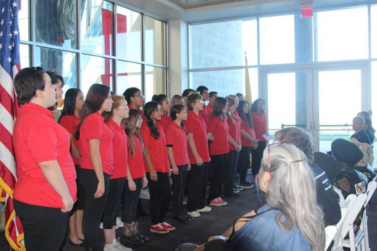Middle school choir in red shirts singing at Salute to Heroes Veterans Day Celebration 2014