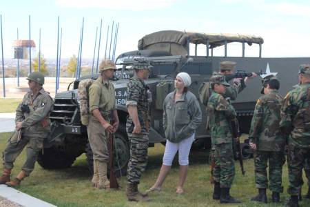 Woman talking with soldiers in uniform in front of military vehicle at Salute to Heroes Veterans Day Celebration 2014