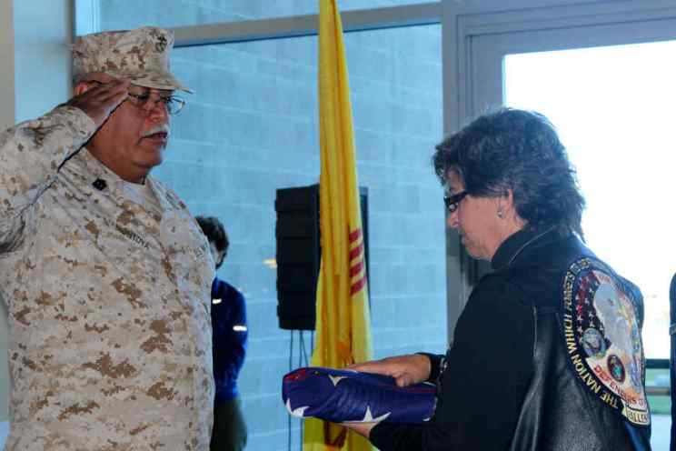 Military Man saluting folded flag at Salute to Heroes Veterans Day Celebration 2014
