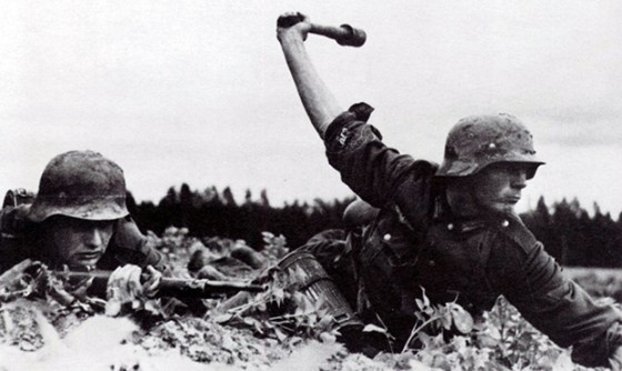 "A German soldier lobs a Model 24 Stielhandgranate, unofficially known as a ""potato masher"". Axis troops also called the ubiquitous stick grenade the ""door knocker""."