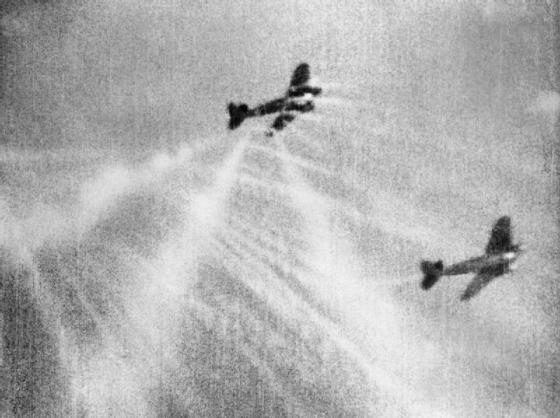 A spitfire unleashes a salvo of gunfire at a pair of German bombers.