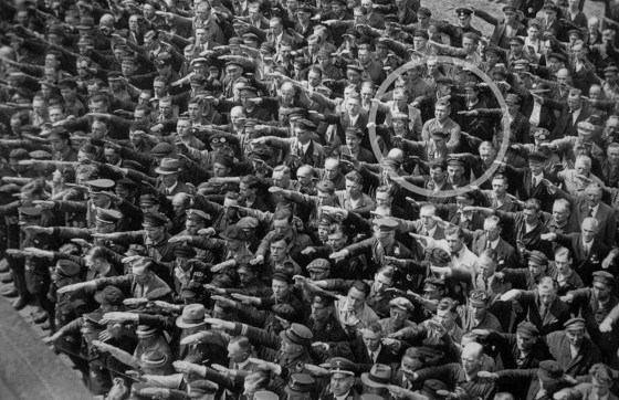 A lone man refuses to perform the Nazi salute at a Hamburg ship launch ceremony in 1936. He was later identified as August Landmesser. (Image source: WikiCommons)