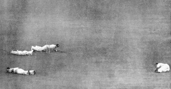 Cricket players throw themselves to the ground as a V-1 flying-bomb strikes near a London pitch.