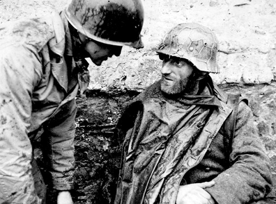 An American GI exchanges a few words with a former enemy turned POW. One veteran, interviewed below, imagines how much he likely had in common with his foes on the other side of the battlefield.