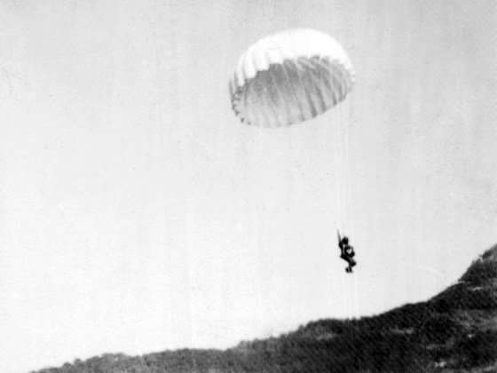 A member of Capt. William Gowdy's B-24 crew parachutes to the ground after bailing out of B-24D #42-40060, THE CHAMP. (Image source: Odis F. Cleere Collection)