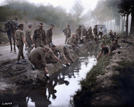 Canadian infantrymen fill their canteens at the side of a road, 1918. (Image source Canada. Dept. of National Defence/Library and Archives Canada via the Vimy Foundation)