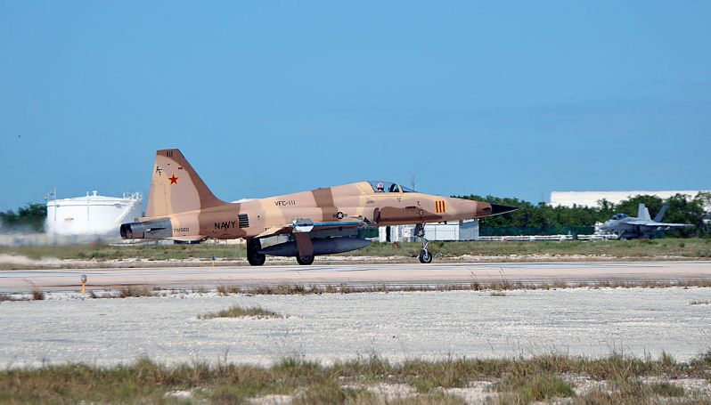 """A U.S. Navy Northrop F-5N Tiger II (BuNo 761560, USAF s/n 76-1560, former Swiss J-3035) assigned to Fighter Squadron Composite (VFC) 111 """"Sundowners"""" launches from Boca Chica Field of Naval Air Station Key West, Florida (USA)."""