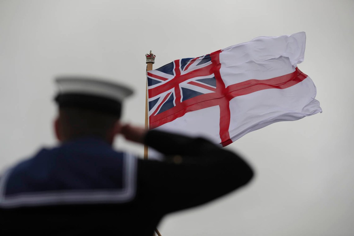The White Ensign being hosted as a sailor salutes onboard HMS Prince of Wales for the first time during her commissioning