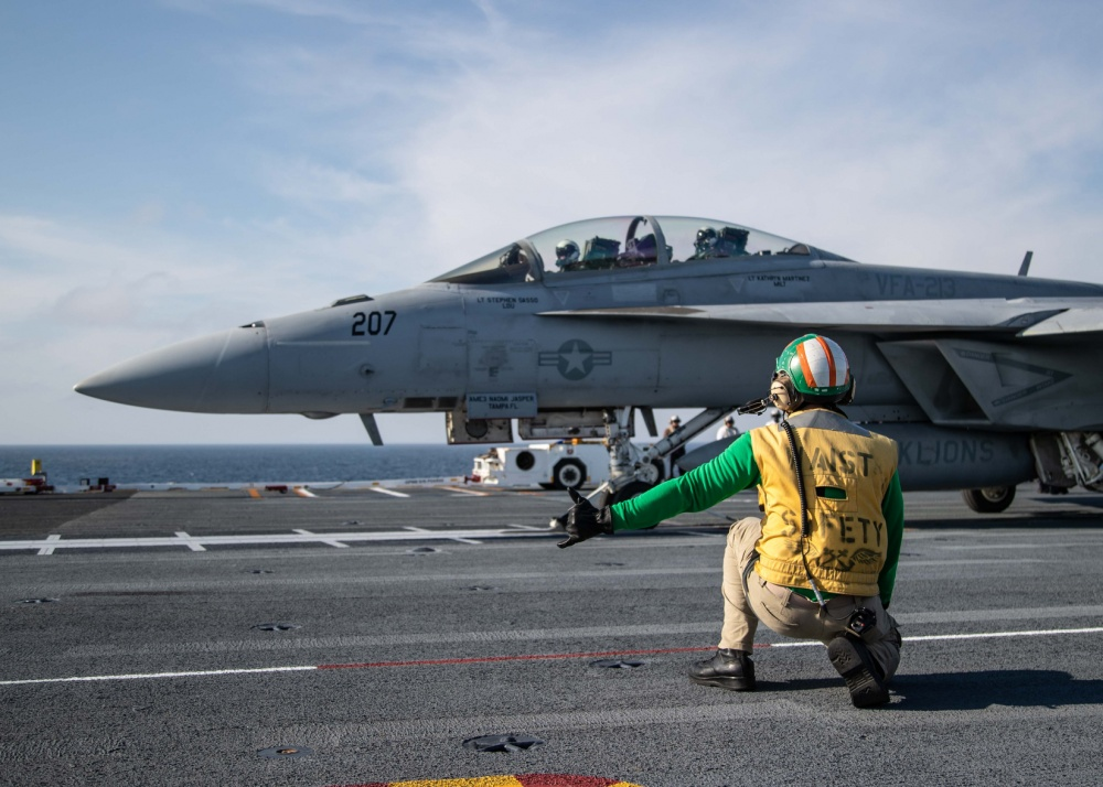 "Chief Aviation Boatswain's Mate (Handling) Louis Mountain, from Seat Pleasant, Maryland, assigned to USS Gerald R. Ford's (CVN 78) air department, signals an F/A-18F Super Hornet, attached to ""Black Lions"" of Strike Fighter Squadron (VFA) 213, on Ford's flight deck during flight operations. Ford is currently underway conducting its flight deck and combat air traffic control center certifications. (U.S. Navy photo by Mass Communication Specialist 3rd Class Zachary Melvin)"