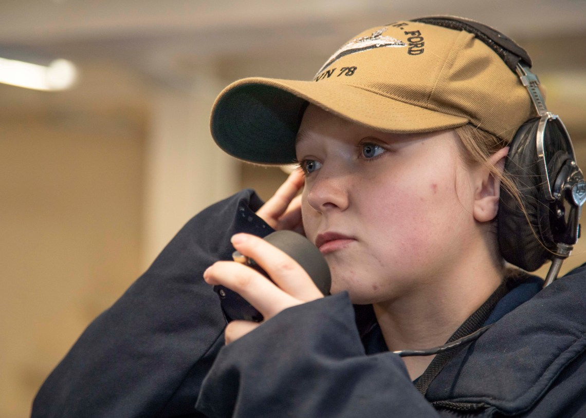 Seaman Mercedes Mendenhall, from Ivanhoe, California, assigned to the deck department of the aircraft carrier USS Gerald R. Ford (CVN 78), speaks into a sound powered telephone during an anchoring evolution in the ship's forecastle.