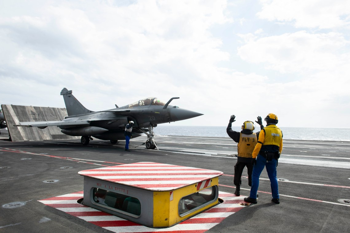 Aviation Boatswain's Mate (Handling) 3rd Class Lauret Price, from Cleveland, left, and a member of the French Marine Nationale, spot a French Dassault Rafale M fighter jet on the flight deck aboard the French aircraft carrier Charles de Gaulle (R 91) while conducting interoperability exercises with the aircraft carrier USS Dwight D. Eisenhower (CVN 69).