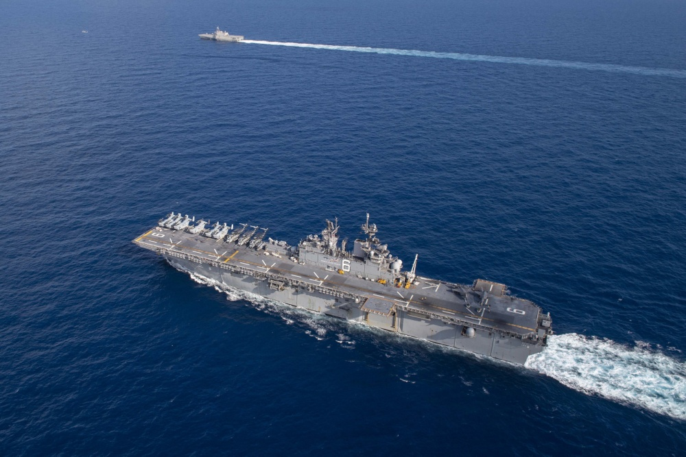 Amphibious assault ship USS America (LHA 6) sails alongside littoral combat ship USS Gabrielle Giffords (LCS 10).