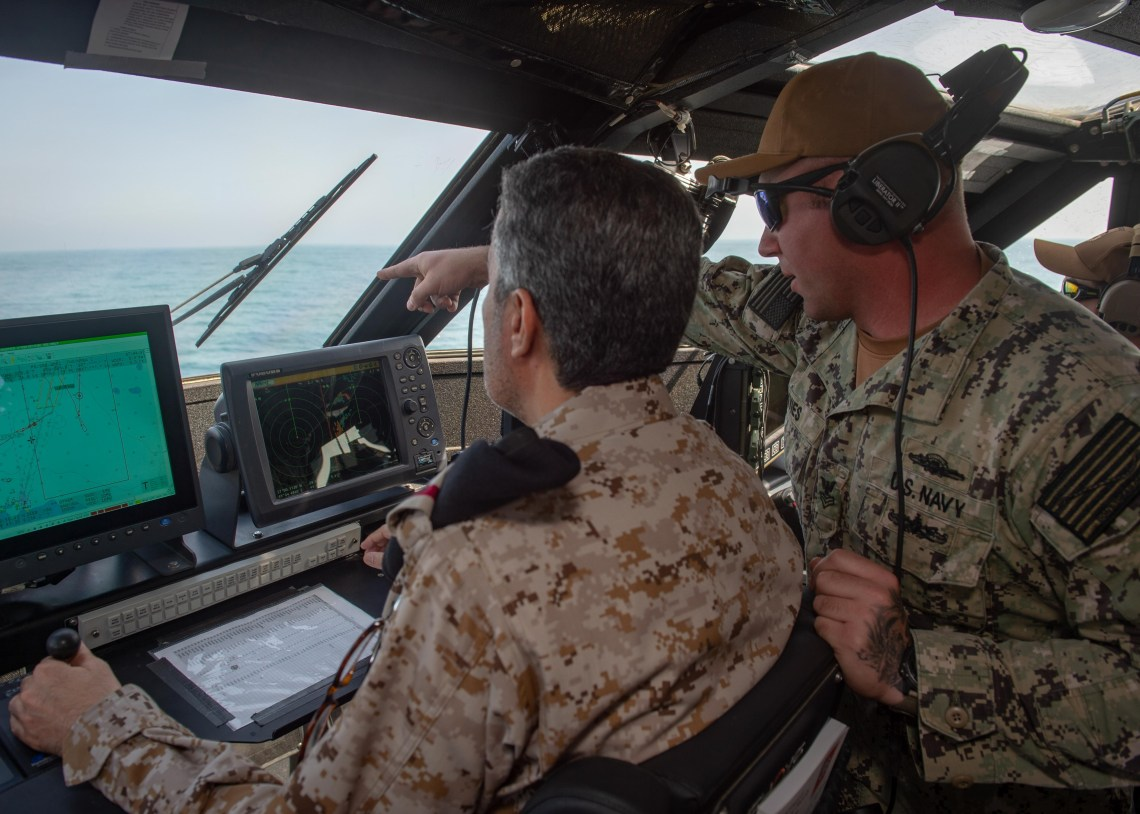 Gunner's Mate 1st Class Andrew Davies, assigned to Commander Task Force 56, guides Rear Adm. Majed Haz'z Al-Kahtani, deputy commander of Royal Saudi Naval Forces (RSNF) Eastern Fleet, on how to operate a Mark VI patrol boat during an underway as part of exercise Nautical Defender 20 in Jubail, Kingdom of Saudi Arabia, Feb. 23, 2020.