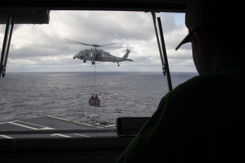 Logistics Specialist 2nd Class Samuel Muzzio, from Newnan, Georgia, assigned to USS Gerald R. Ford's (CVN 78) supply department, observes an MH-60S Sea Hawk helicopter, attached to Helicopter Sea Combat Squadron (HSC) 9, from the pilot house during a vertical replenishment-at-sea with USNS Joshua Humphreys (T-AO 188) March 24, 2020. Ford is underway in the Atlantic Ocean conducting carrier qualifications. (U.S. Navy photo by Mass Communication Specialist 3rd Class Brett Walker)