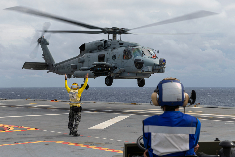 Leading Seaman Aviation Support Jarryd Jinks marshals embarked MH-60 Romeo helicopter 'COBRA 15', as it prepares to land onboard HMAS Adelaide during First of Class Flight Trials.