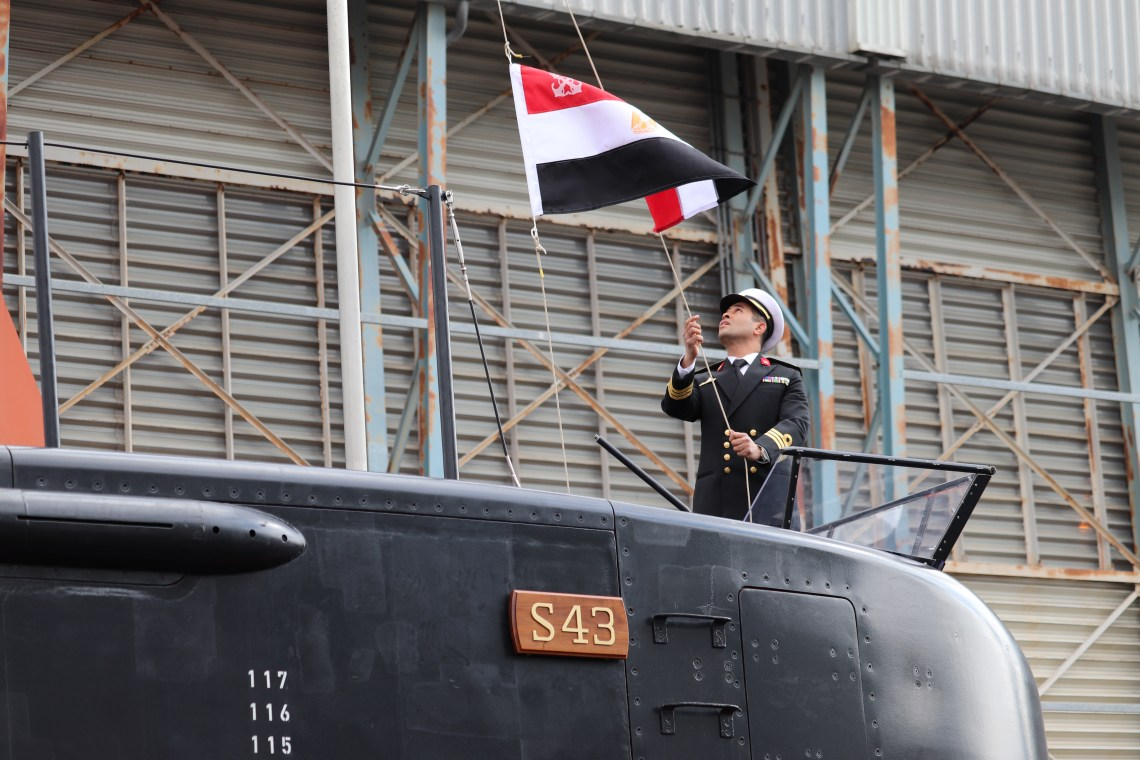 An Egyptian Navy officer symbolically raises the national flag on the fin of the third Type 209/1400mod diesel-electric submarine handed over in Kiel by ThyssenKrupp Marine Systems. (TKMS photo)