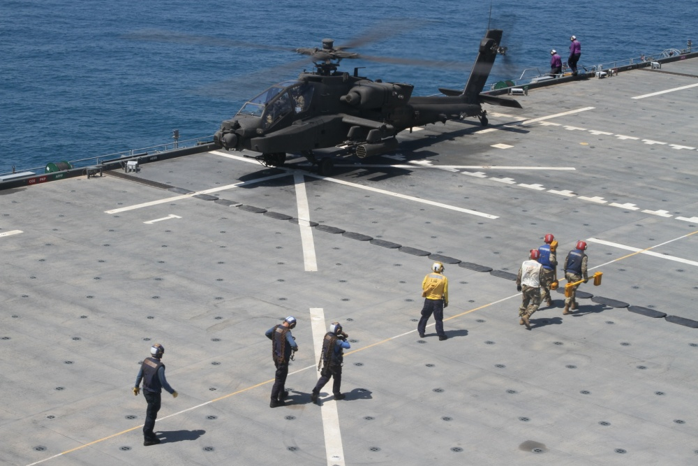 U.S. Navy deck crew gets into position to secure an AH-64E Apache gunship to the deck of the U.S.S. Lewis B. Puller during an at sea training exercise on April 16, 2020 in the Persian Gulf. The U.S. Army and the U.S. Navy work together to not only train but also make both forces more effective. (U.S. Army photo by SGT. Andrew Winchell)