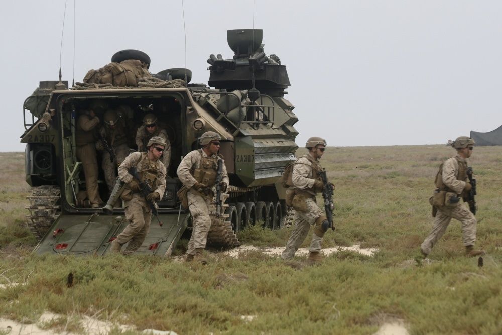 Marines assigned to Golf Company, Battalion Landing Team 2/8, 26th Marine Expeditionary Unit (MEU), exit an assault amphibious vehicle during an amphibious raid training evolution on Karan Island, Saudi Arabia, April 20, 2020. The Bataan Amphibious Ready Group and 26th MEU are conducting routine sustainment training in the U.S. 5th Fleet area of operations in order to enhance the Navy-Marine Corps team's ability to employ low-signature, operationally relevant and strategically mobile crisis response forces to project power over key maritime terrain. (U.S. Marine Corps photo by Staff Sgt. Pablo Morrison)