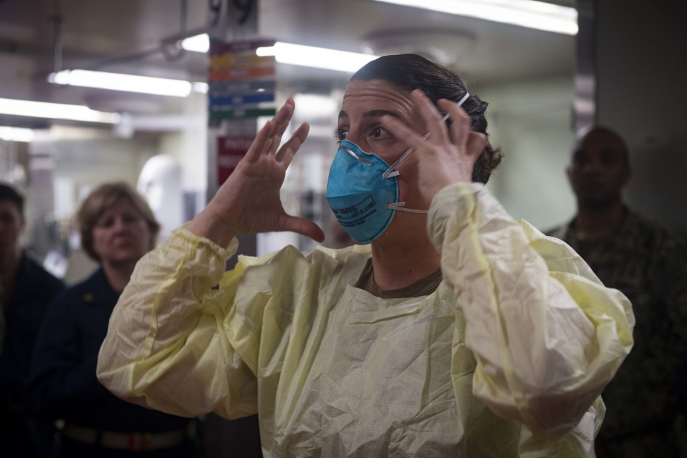 Lt. Cmdr. Nevin Yazici demonstrates how to properly fit an N95 respiratory protective device aboard hospital ship USNS Comfort (T-AH 20) as the ship prepares to admit patients in support of the nation's COVID-19 response efforts.