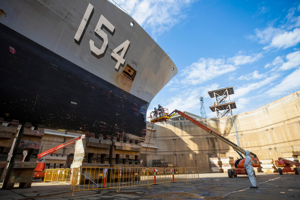 Defence contractors conduct maintenance on HMAS Parramatta during her refit in the Captain Cook Graving Dock at Garden Island, Sydney, NSW.