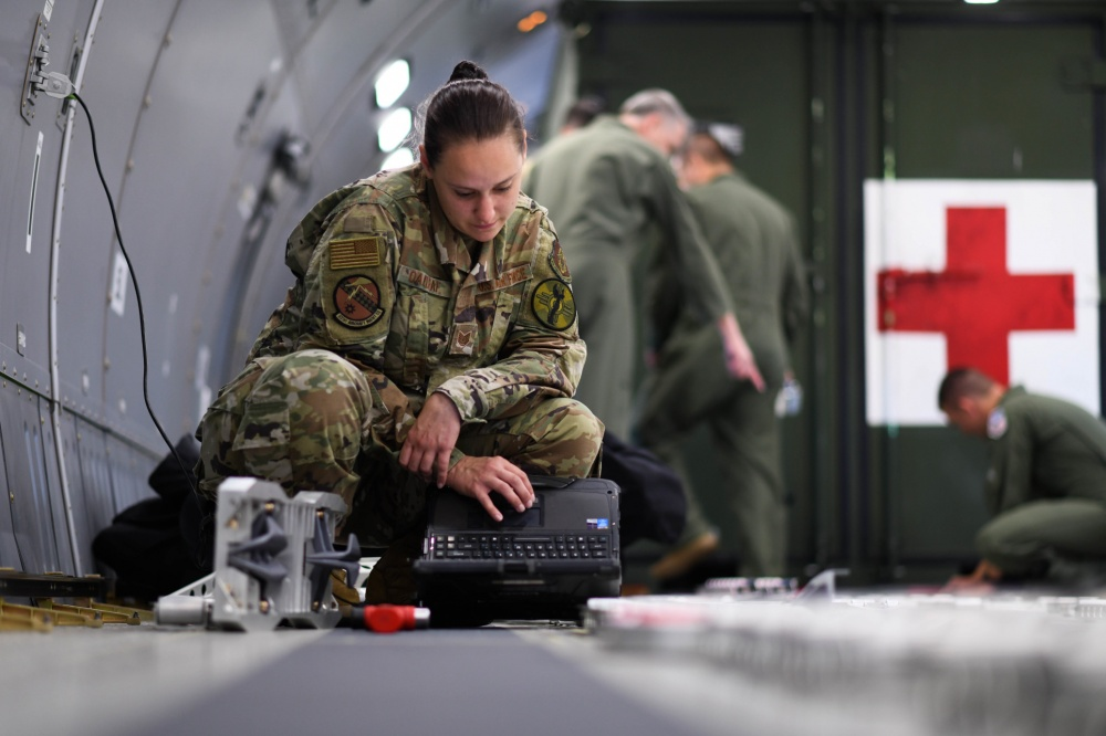 Tech. Sgt. Leah Oakleaf, 931st Aircraft Maintenance Squadron crew chief assigned to McConnell Air Force Base, Kansas reviews her technical order for configuration plans of the fuselage cargo palette locks.
