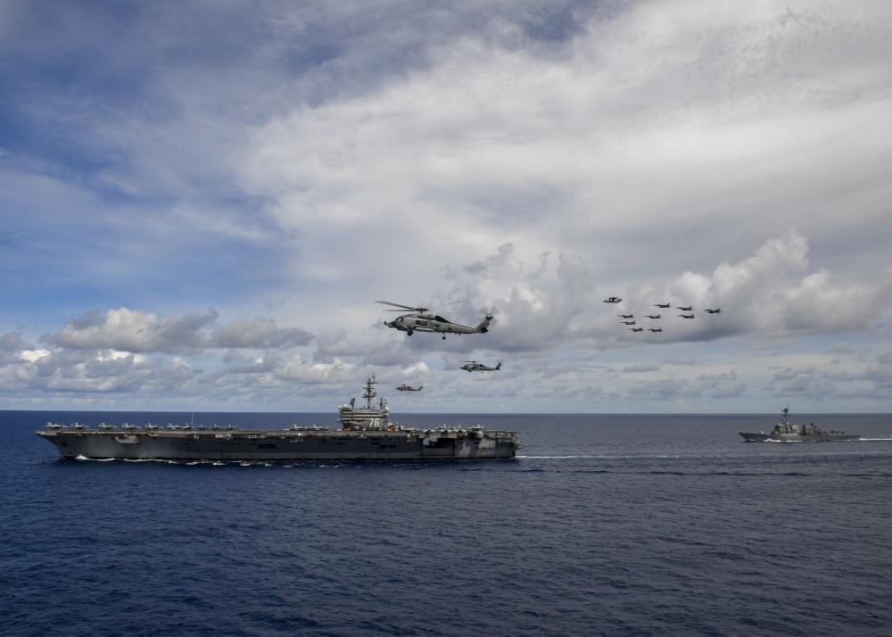 Aircraft from Carrier Air Wing 5 and Carrier Air Wing 17 fly in formation over the Nimitz Carrier Strike Force (CSF).