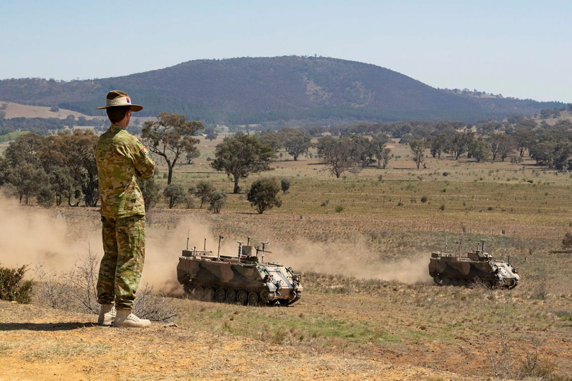 Australian Army officer Brigadier Ian Langford, DSC and Bars, watches on as two autonomous M113 AS4 optionally crewed combat vehicle (OCCV) assault an enemy position at the Majura Training Area, Canberra.