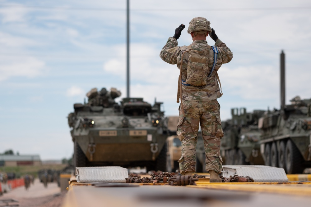 Staff Sgt. Shawn Mercer, a cavalry scout assigned to Alpha Troop, 4th Squadron, 10th Cavalry Regiment, 3rd Armored Brigade Combat Team, 4th Infantry Division, guides a Stryker onto a railcar at Fort Carson, Colorado,