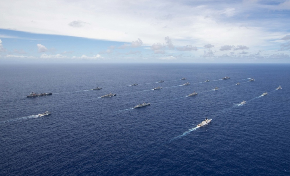 Multinational navy ships and a submarine steam in formation during a group sail off the coast of Hawaii during Exercise Rim of the Pacific (RIMPAC) 2020, August 21.
