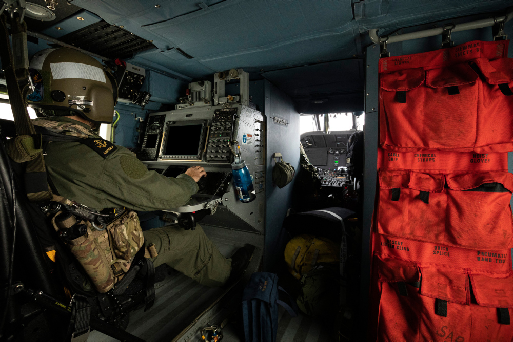 Royal Australian Navy sailor, Leading Seaman Aircrewman Dylan Skipsey operates the MH-60R Seahawk console in the rear of the aircraft during a photography exercise on the 18th September 2019.