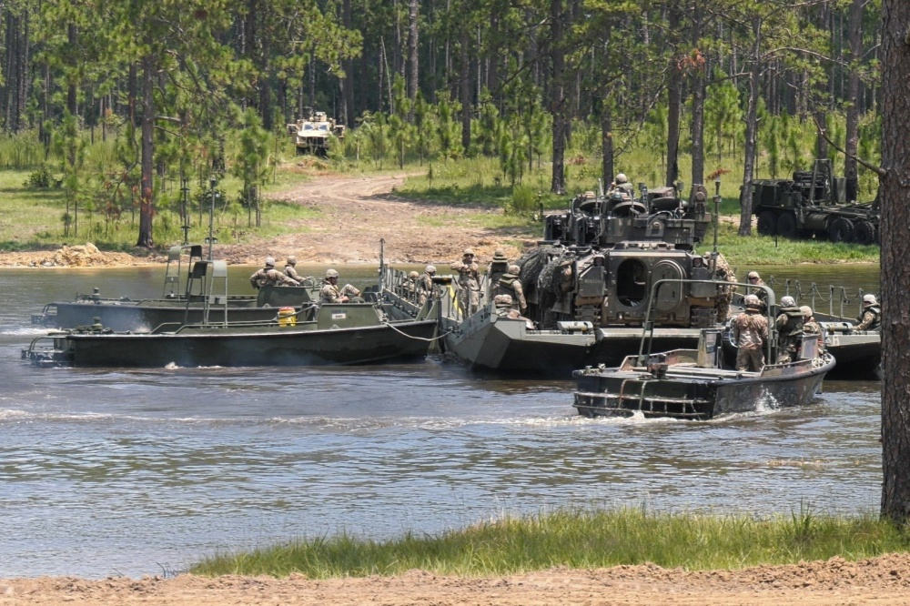 Soldiers from the 926th Engineer Brigade move two M2 Bradley Fighting Vehicles across Pineview Lake on a ribbon raft, July 17, 2020, at Fort Stewart, Georgia.