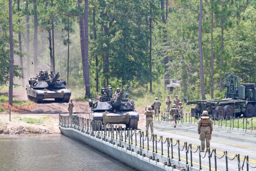 M1 Abrams Tank crews from 3rd Battalion, 69th Armored Regiment, 1st Armored Brigade Combat Team, 3ID, maneuver their tanks over an improved ribbon bridge, July 17, 2020, during a wet gap crossing exercise at Pineview Lake, Fort Stewart, Georgia.